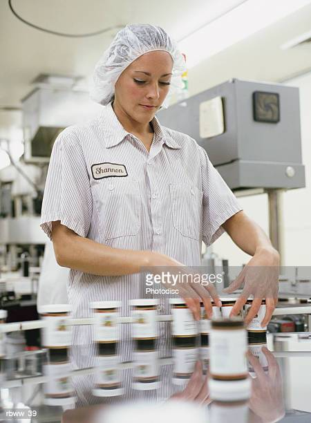 a caucasian woman inspects bottles of pills on a clean-room assembly line