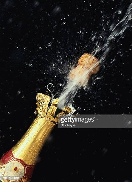 a champagne cork shooting out of a champagne bottle