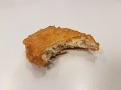 a delicious chicken nugget with a bite taken out of it