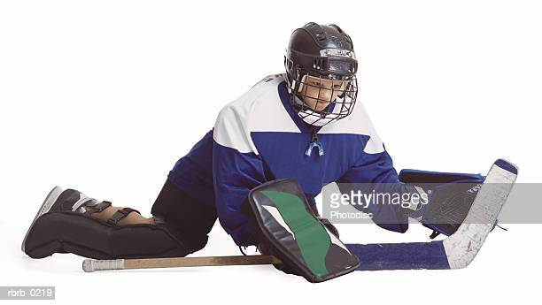 a child caucasian male hockey player in blue and white serving as goalie dives to the ground to block a shot
