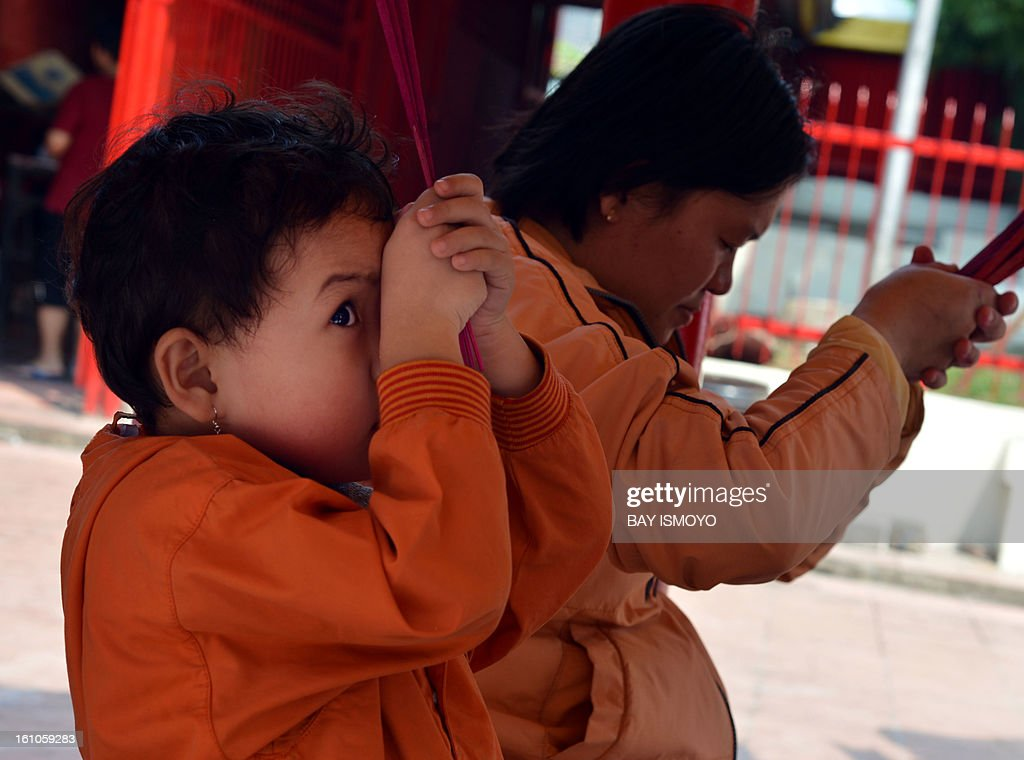 a Chinese ethnic girl peeps as she and her mother pray at a Chinese temple in the Indonesian capital city of Jakarta on February 9, 2013 the country's minority Chinese-Indonesians prepare to celebrate the Chinese New Year. The Year of the Snake falls across the region on February 10. AFP PHOTO / Bay ISMOYO