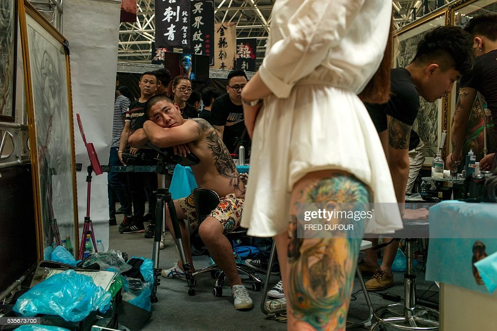 a chinese man gets a tattoo on his back at the Langfang International Tattoo show, in Hebei province, on May 29, 2016. / AFP / FRED