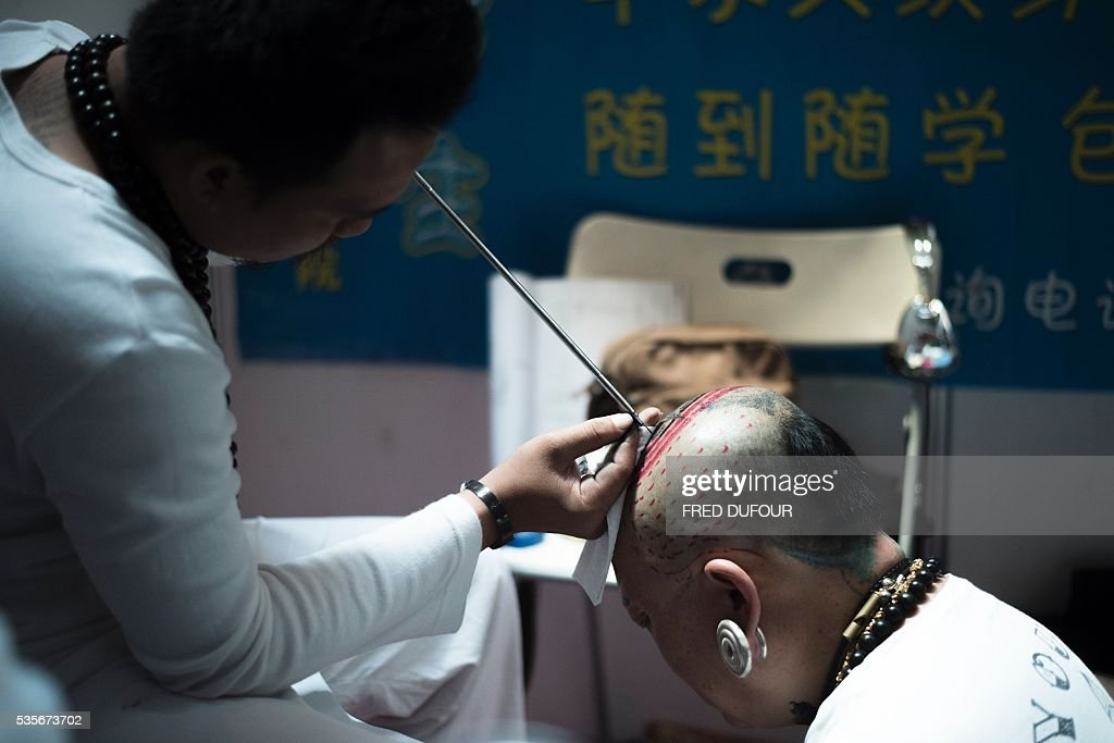 a chinese man gets a tattoo on his head at the Langfang International Tattoo show, in Hebei province, on May 29, 2016. / AFP / FRED