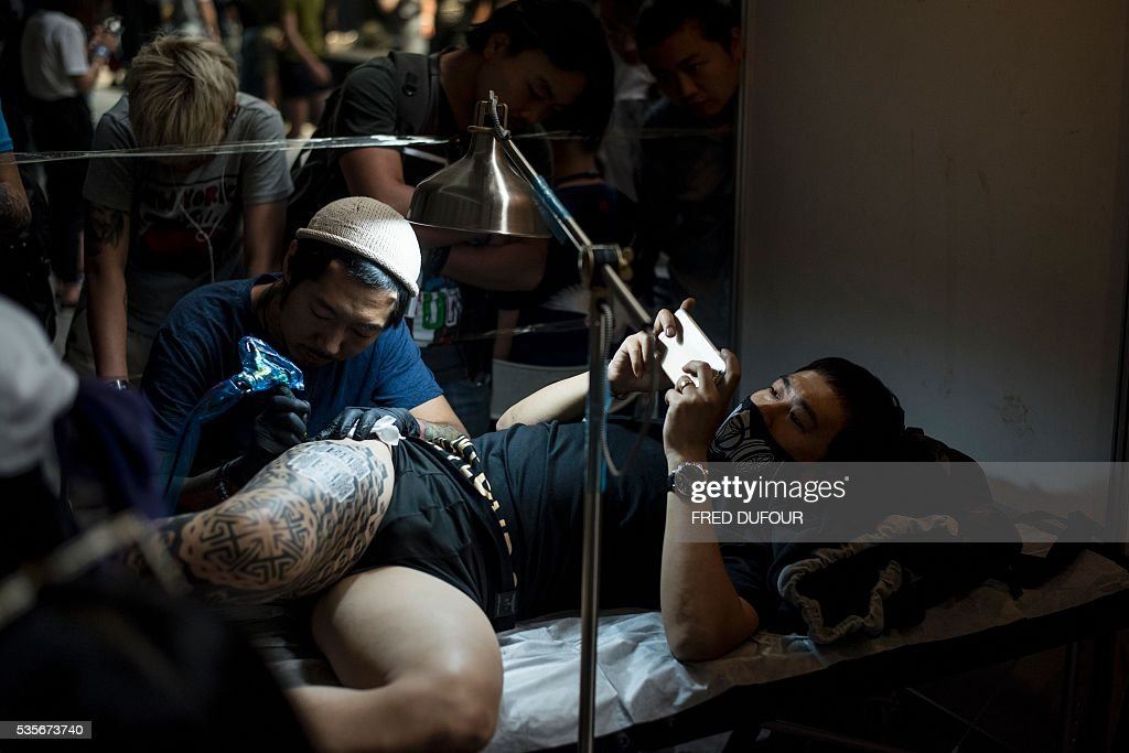 a chinese man gets a tattoo on his leg at the Langfang International Tattoo show, in Hebei province, on May 29, 2016. / AFP / FRED