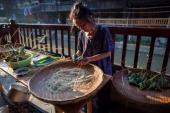 CONTENT] a Chinese woman making Zongzi on Dragon Boat Festival at Zhaoxing Dong villageGuizhou