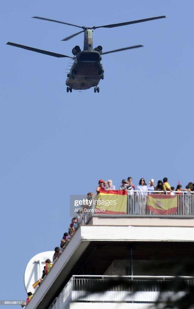 a combat helicopter overflies spectators during the Spanish National Day military parade in Madrid on October 12, 2017. A Spanish Eurofighter jet crashed today after taking part in a military display in Madrid for Spain's national day, killing its pilot, the defence ministry said. Spain marks its national day under high tension as the country reels from the biggest challenge to unity in a generation with its Catalan region threatening to break away. /