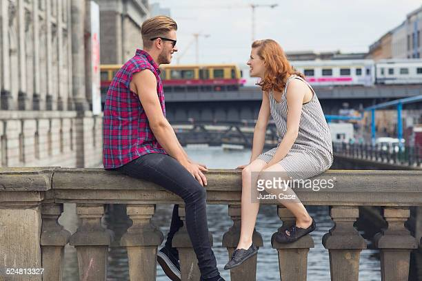 a couple is sitting on a city bridge
