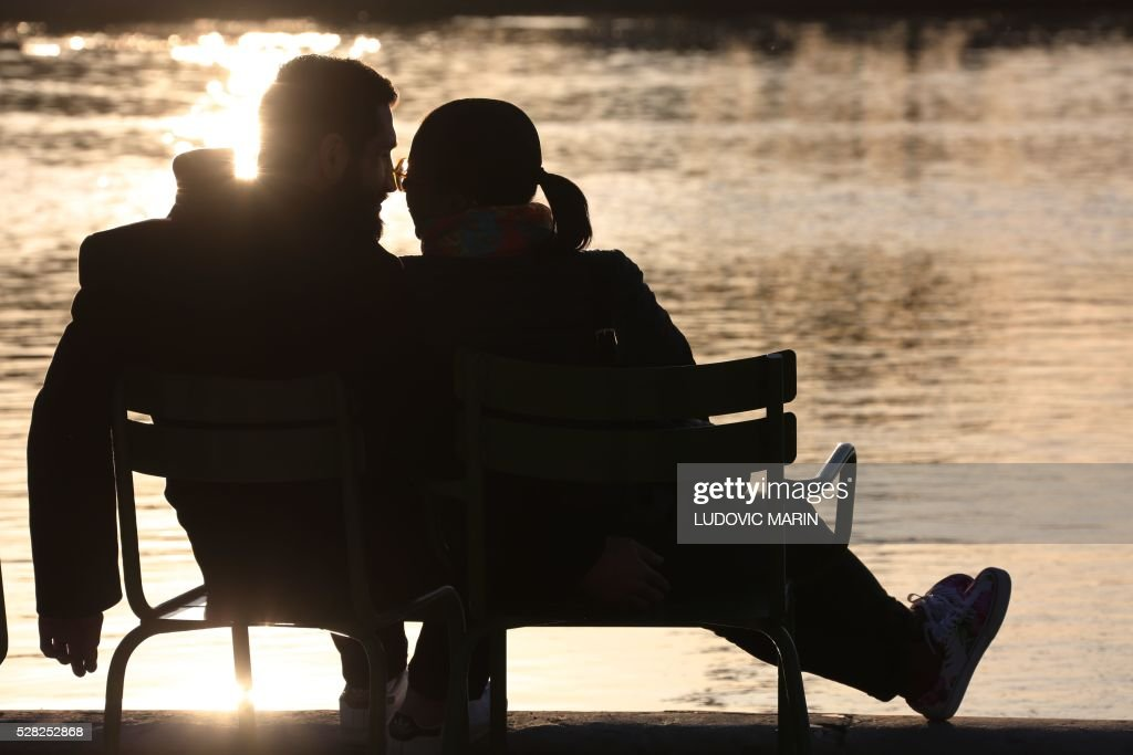 a couple kisses in the Tuileries garden at sunset, in Paris, on may 4, 2016. / AFP / LUDOVIC