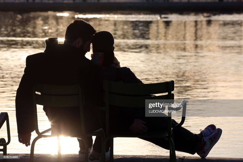 a couple takes a break in the Tuileries garden at sunset, in Paris, on may 4, 2016. / AFP / LUDOVIC