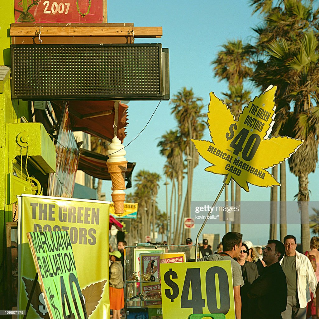 CONTENT] a crowd gathers around a medical marijuana (cannabis) dispensary on the venice beach oceanfront boardwalk in los angeles, ca.