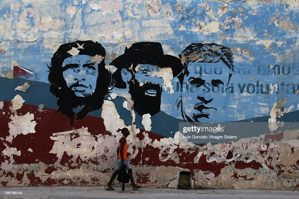 CONTENT] a cuban walks by a mural in an advanced state of decay (a metaphor for the dilapidation in old havana and the state of politics in the island) depicting famous revolutionaries: the che guevara, camilo cienfuegos and julio antonio mella (founder of the cuban communist party). these murals go by the famous sentence 'study, work, rifle', quoted from a 1960 speech by osvaldo dorticós (then president of cuba) which became not only the rebel youth association (ARJ) motto but a catchphrase in the cuban education system.