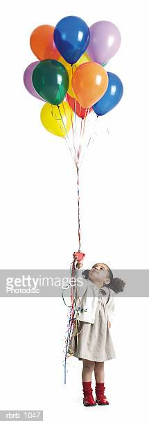 a cute little african american girl holds and looks up at a bundle of balloons