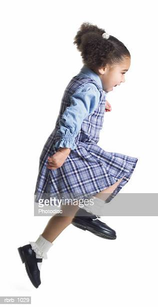 a cute little african american girl in a purple dress runs and jumps up playfully into the air