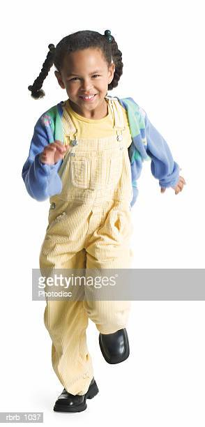 a cute little african american girl in yellow overalls playfully runs forward and smiles