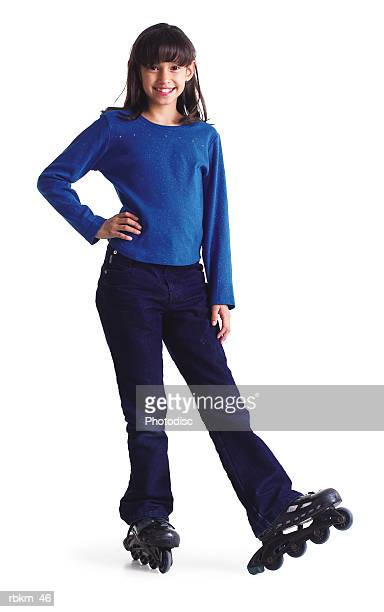 a cute little ethnic looking girl smiles as she stops on her roller blades
