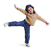 a cute little girl throws out her arms and kicks into the air while dancing
