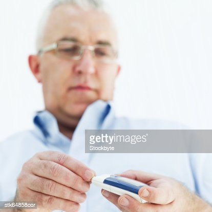 a diabetic using a glucometer : Stock Photo
