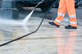 a dustman with a pressure washer cleaning the street