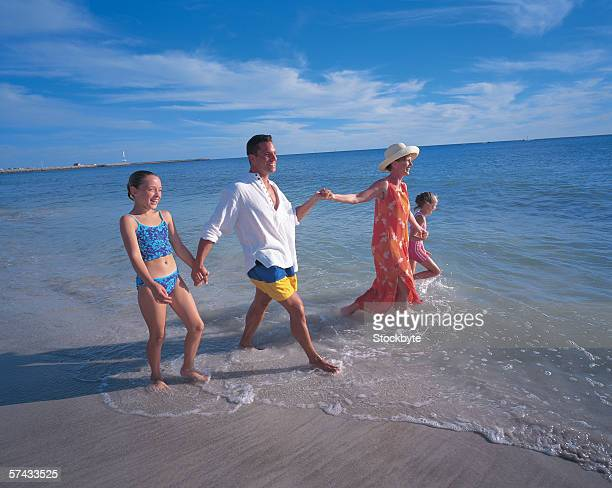 a family holding hands and walking together on a beach