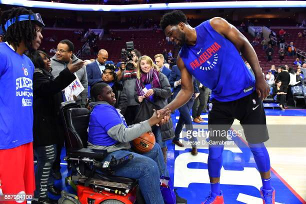 a fan shakes hands with Joel Embiid of the Philadelphia 76ers before the game against the Los Angeles Lakers on December 7 2017 at Wells Fargo Center...