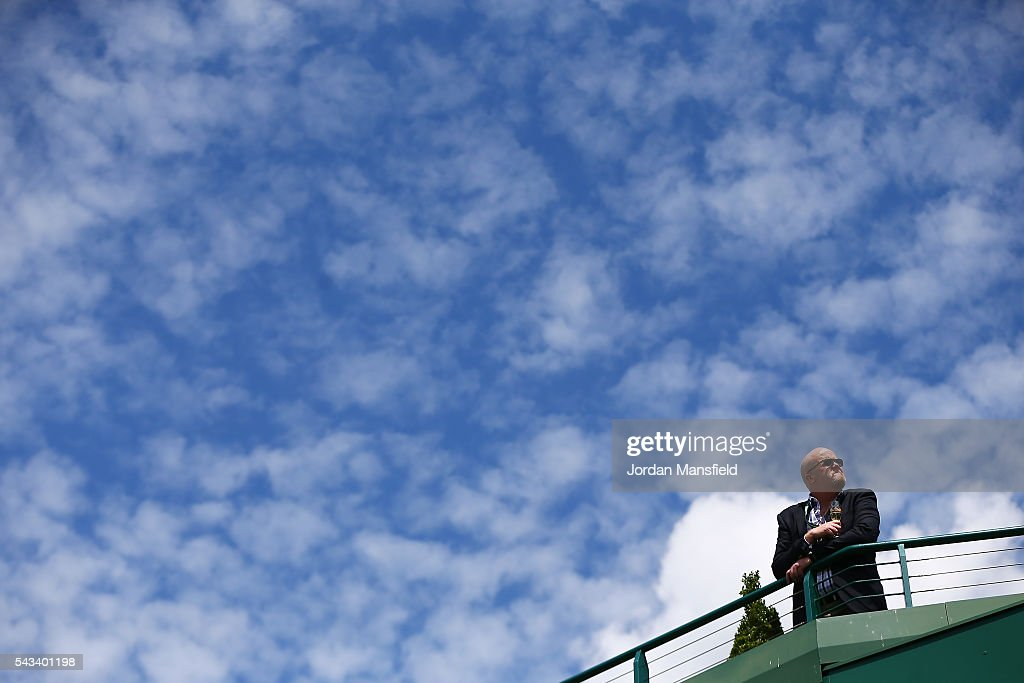 a fan watches on from the balcony on day two of the Wimbledon Lawn Tennis Championships at the All England Lawn Tennis and Croquet Club on June 28, 2016 in London, England.