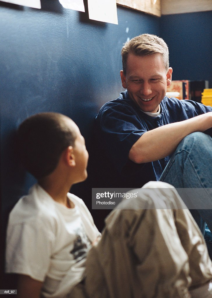 a father and son sit on the floor and talk