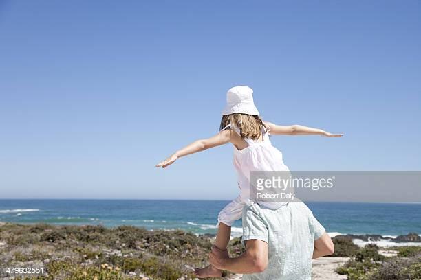 Um pai dando sua filha um piggy back ride