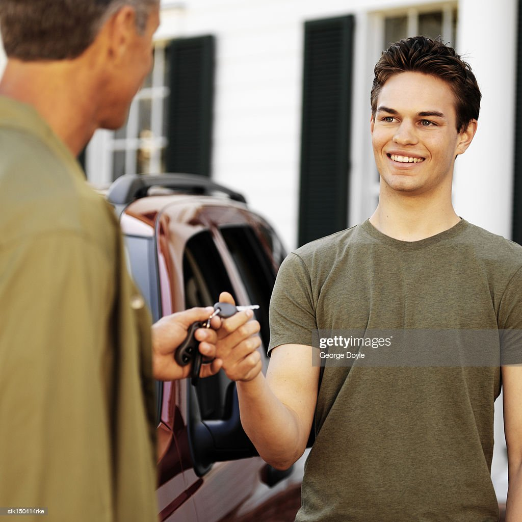 a father giving the cars keys to his son : Stock Photo