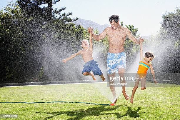 a father playing with his children in a sprinkler