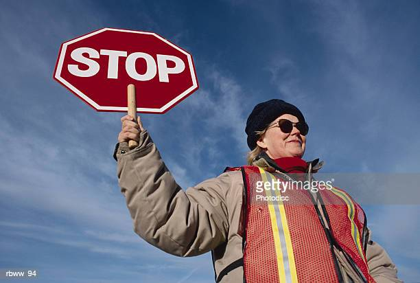 a female caucasian wearing sunglasses and a wool cap holds a stop sign at a crosswalk