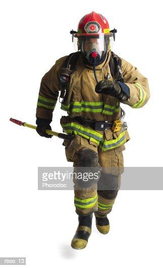 a firefighter in full gear runs forward carrying a fire axe