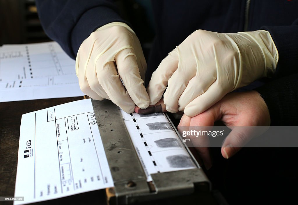 a Forensics expert takes the fingerprints of a person during a mock exercise to present the work of a Police Technique et Scientifique (PTS, technical and scientific police) unit, on January 25, 2013 at Poissy, west of Paris. AFP PHOTO THOMAS SAMSON