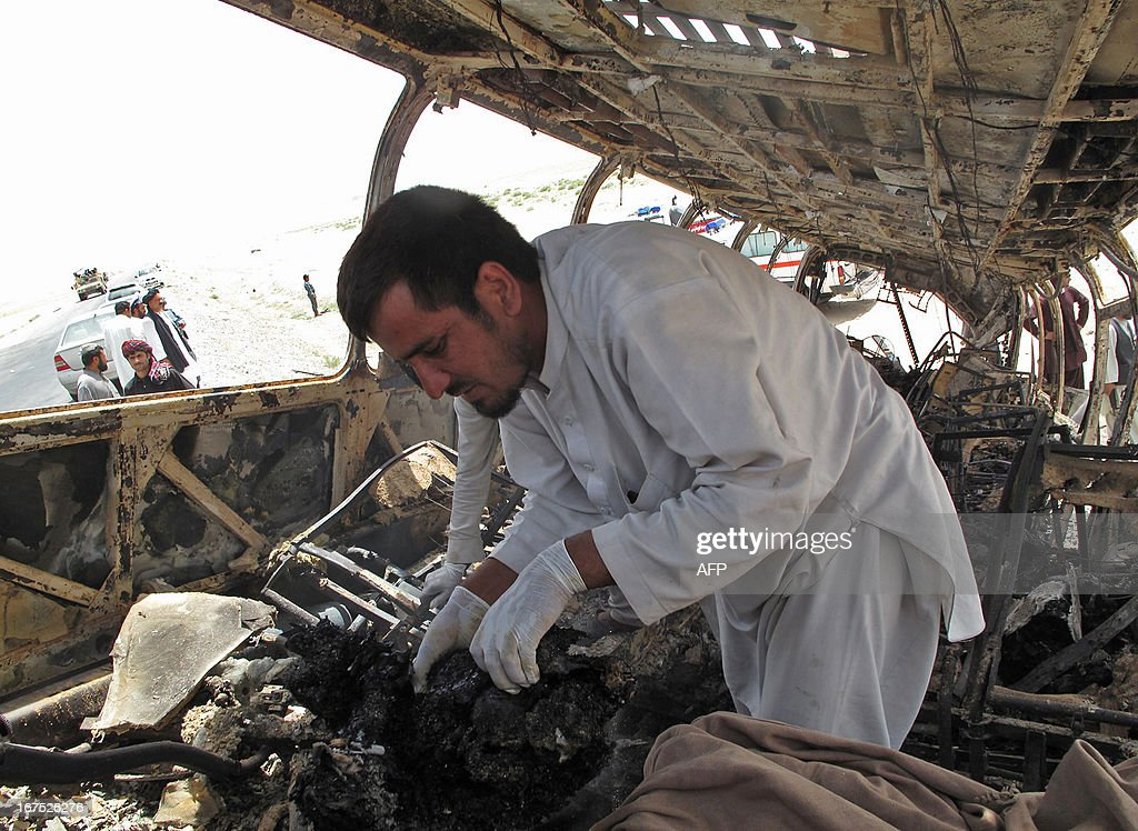 a forensics official collects evidence at the scene where a passenger bus collided with a fuel tanker truck in Kandahar province on April 26, 2013. A passenger bus in Afghanistan collided Friday with a wrecked fuel tanker left on a road after a Taliban insurgent attack, killing at least 45 people, officials said. AFP PHOTO/Noor MOHAMMAD