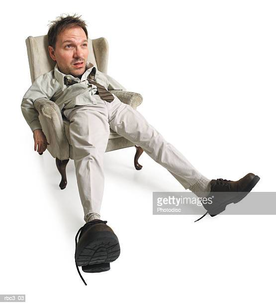a frazzled caucasian man sits in his chair and sticks his feet out while looking exhausted