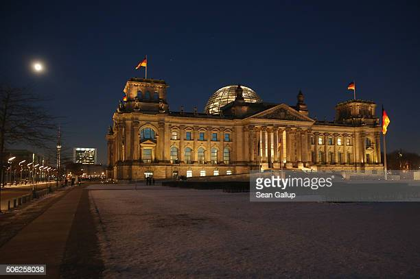 a full moon shines over the Reichstag and its snowcovered lawn on January 22 2016 in Berlin Germany The Reichstag is the seat of the Bundestag...