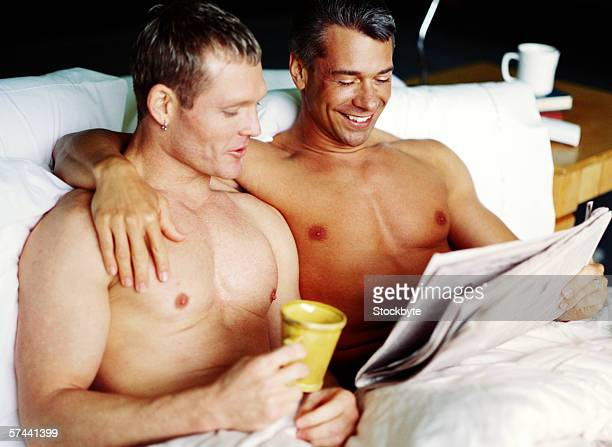 a gay couple lying in bed together and reading the newspapers