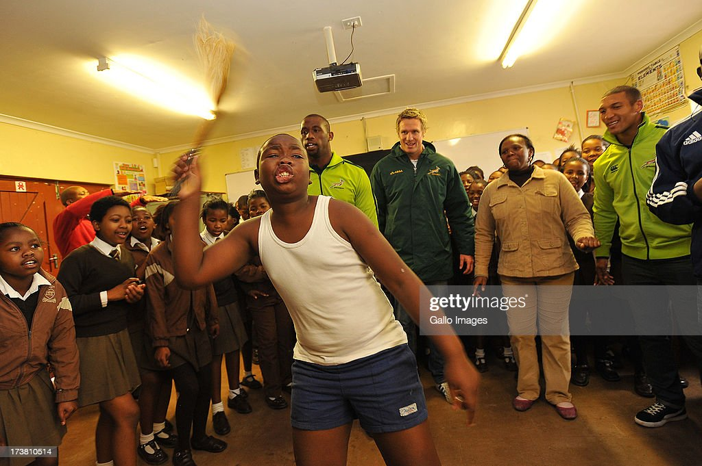 a general view of a young boy doing a traditional dance in honor of Nelson Rolihlahla Mandela's birthday as Jean de Villiers, Siya Kolisi and Gio Aplon looks on during the SA Rugby's 67 minutes in honour of Nelson Mandela Day at Siyabulela Primary School on July 18, 2013 in Cape Town, South Africa.