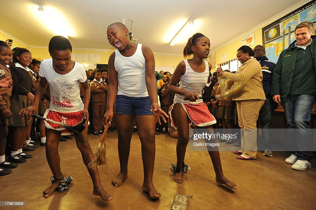 a general view of kids doing a traditional dance in honor of Nelson Rolihlahla Mandela's birthday during the SA Rugby's 67 minutes in honour of Nelson Mandela Day at Siyabulela Primary School on July 18, 2013 in Cape Town, South Africa.