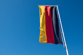 a German flag blows in front of a blue sky