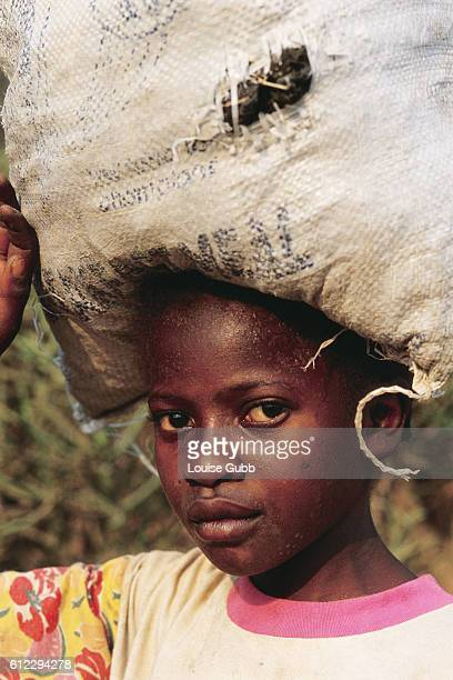 a girl carries a bag of treated human waste home from Kitwe Sewerage Plant The waste can be used as fertilizer in vegetable gardens Buying or growing...