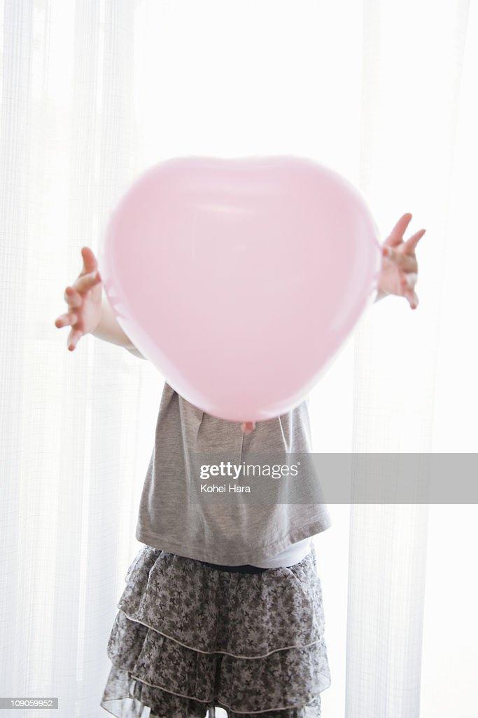 a girl holding a balloon : Stock Photo