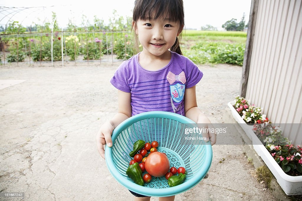 a girl holding a basket with vegetables : Stock Photo