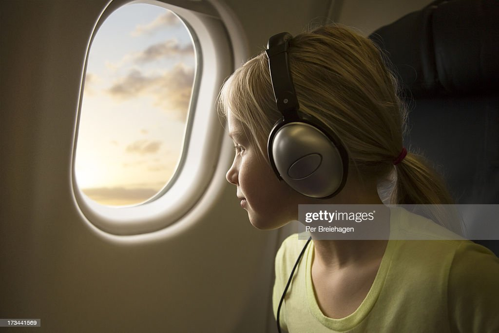 a girl in an airplane looking out of the window : Stock Photo