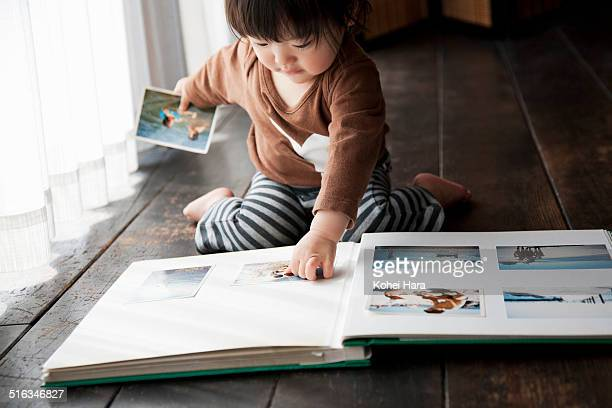 a girl organizing pictures in an album