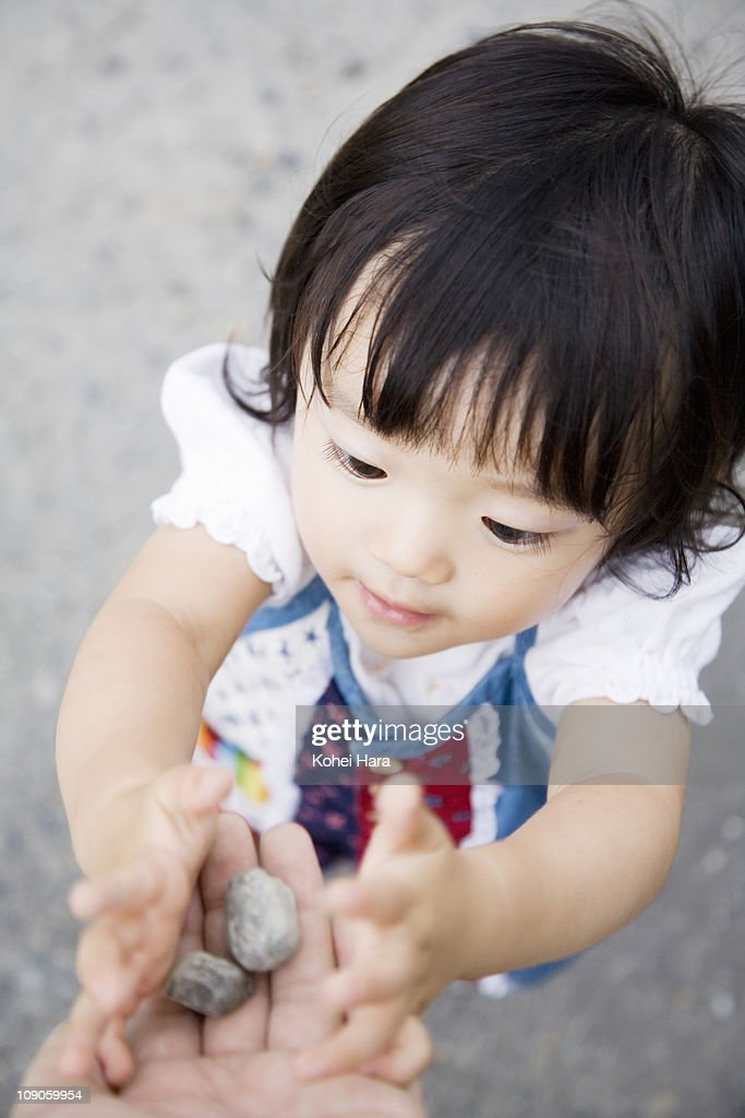 a girl playing with small stones : Stock Photo