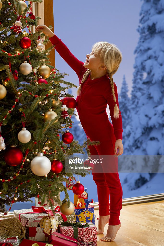 a girl reaching for ornament on Christmas tree : Stock Photo