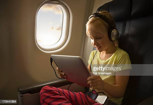 a girl watching a movie on a tablet in an airplane