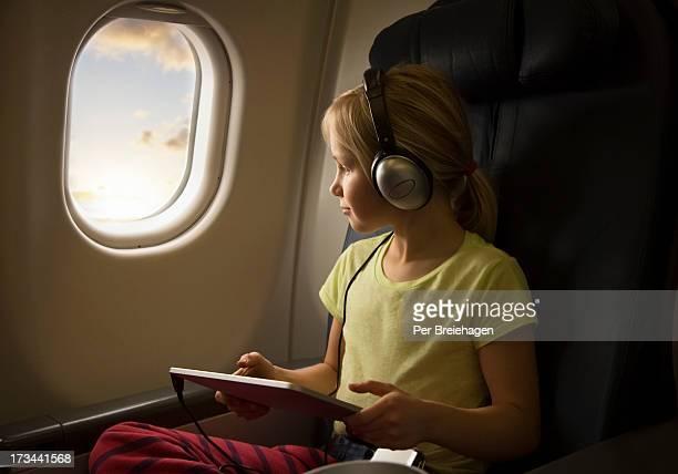 a girl with an ipad on an airplane