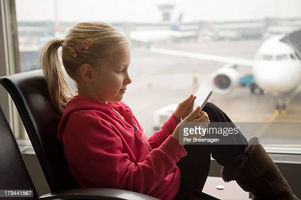 a girl with an iPad at an airport