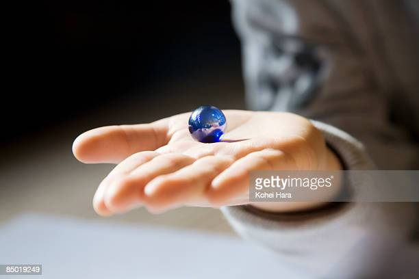 a glass marble on boy's hand